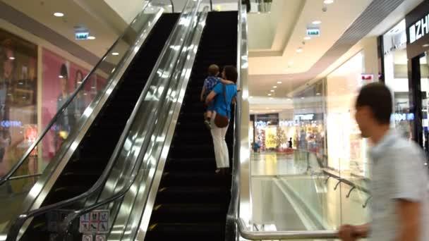 Lidé jedoucí na eskalátoru v obchodním centru