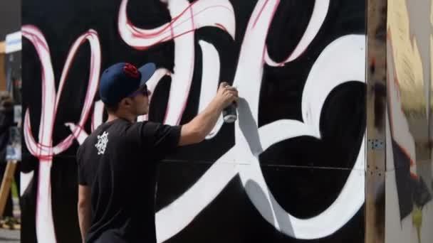 Young man drawing graffiti text
