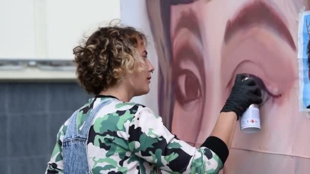 Graffiti painter making female portrait