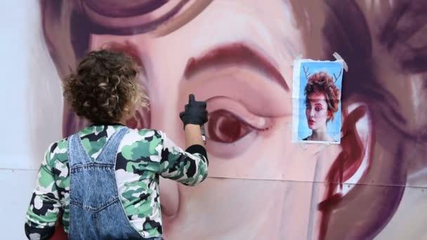 Artist drawing female graffiti portrait