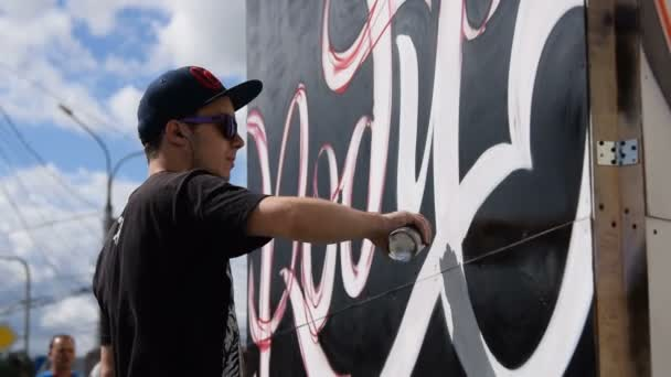 Young graffiti artist working in the street