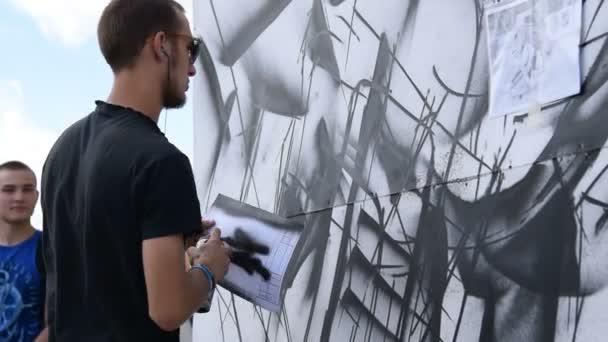 Man performing graffiti skills in the street