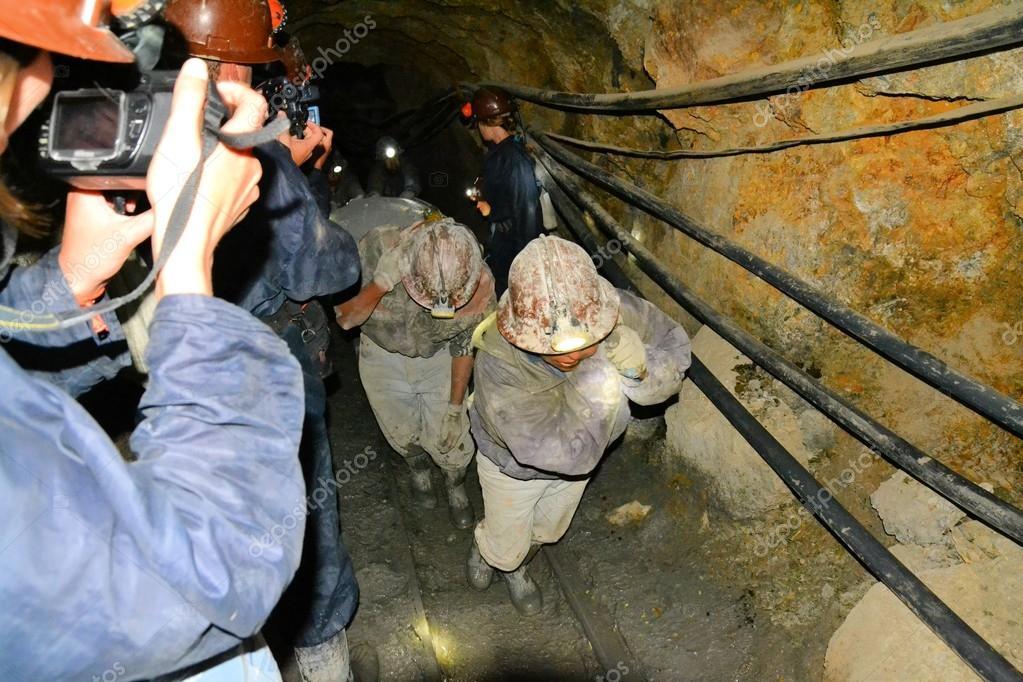 Tourists film miners inside of Cerro Rico mine in Potosi, Bolivia