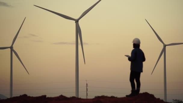 Žena inženýr na pozadí s větrnými mlýny za soumraku