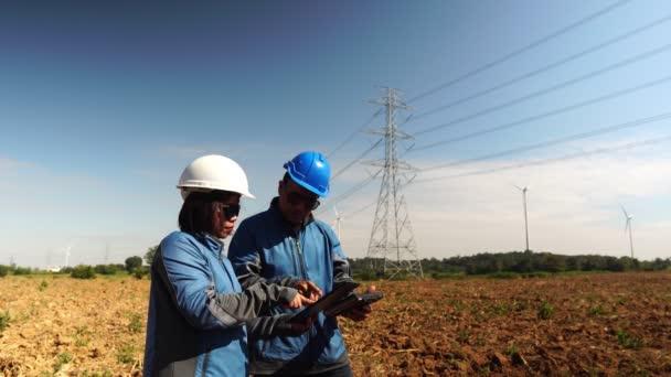 Dva inženýři spolupracující na poli s elektrickými tyčemi na pozadí