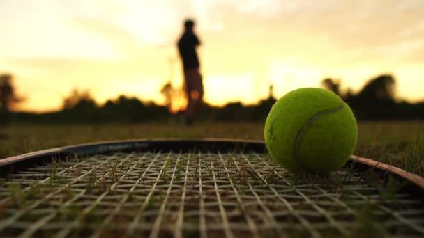 detailní záběry tenisové rakety a míče, rozmazaný tenista ve hře v pozadí