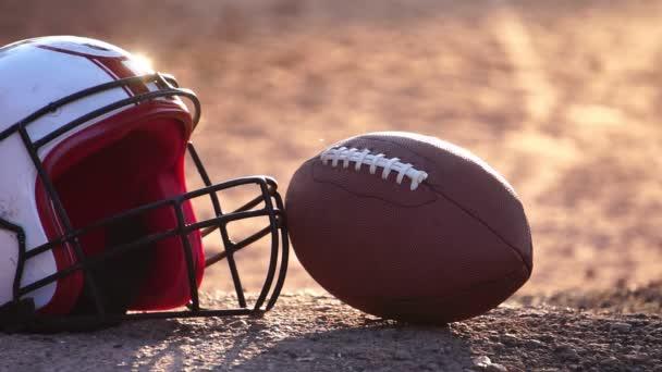 Footage Lassú mozgás: amerikai futball sisak és a játékos emel labdarúgó labdát a naplementében