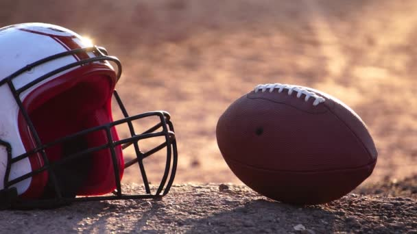 Footage Slow Motion: American Football helmet and player raises football ball at the sunset