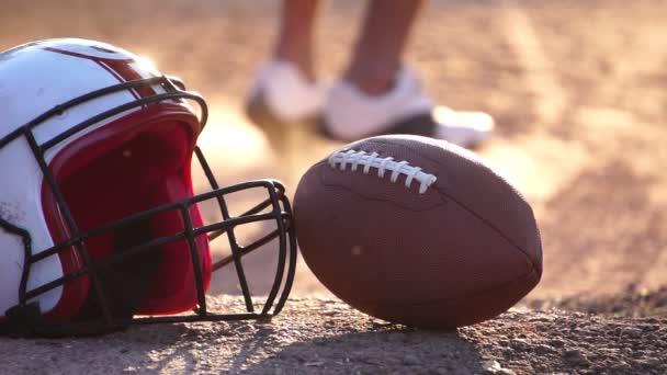 footage slow motion: amerikai futball sisak labdarúgó labda a földön, és a játékos fut a háttérben