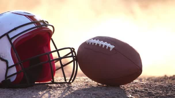 footage slow motion: amerikai futball sisak focilabdával a földön