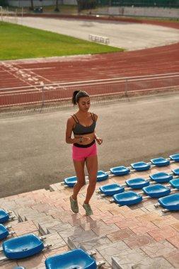 Full length shot of motivated young female runner training on the stadium outdoors