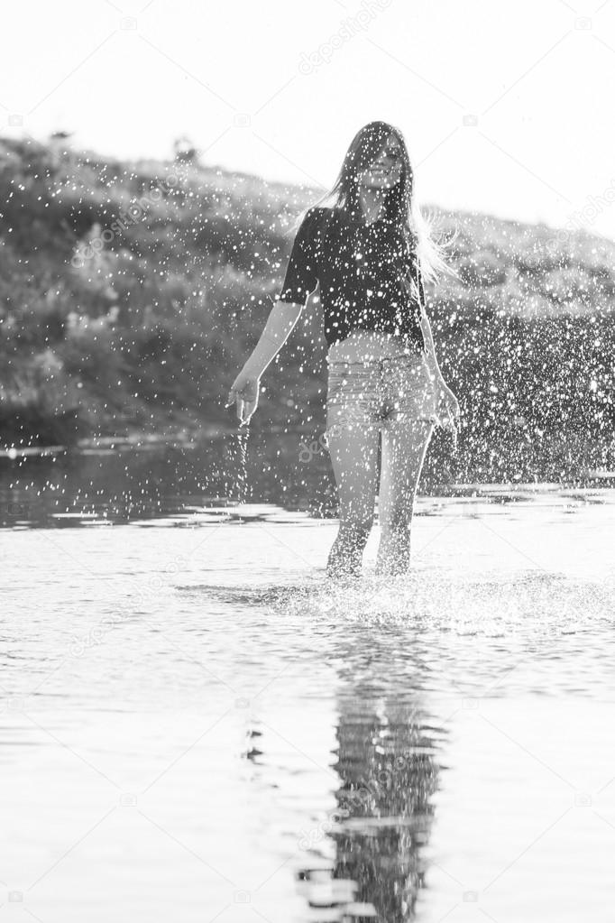 Beautiful girl with long, straight hair posing and playing with water in a small river. Black and white, artistic photography