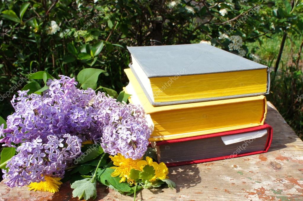 A stack of books in the garden. A stack of thick books and flowers of a lilac in the garden