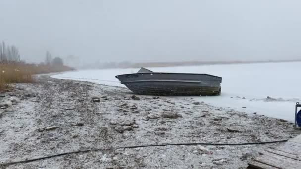Snow-covered old metal fishing boat lies in the snow on the shore of a frozen sea without people. Fishing season has come to an end. Snowfall on lake or river.