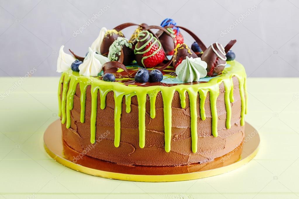 Chocolate birthday cake with fruit and green glaze Stock Photo