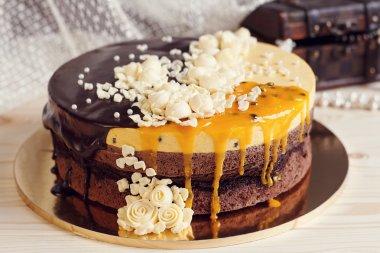 Romaantic cake with chocolate glaze, cream flowers and  mango pa