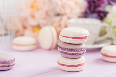 Pastel colored macaroons with floral background