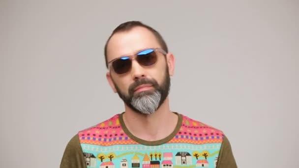Adult bearded man in sunglasses posing