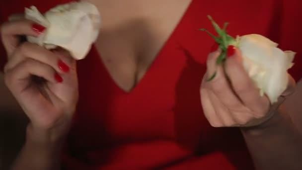 Romantická žena v červených šatech s růží a svíčky