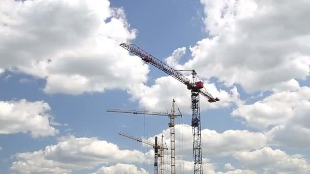 Cranes Working on Construction Site Under Cloudy Sky