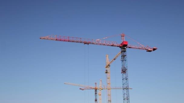 Jeřáby, pracující na stavbě za jasné modré nebe