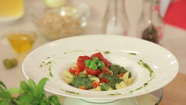 Prezentace těstovin s zeleným pestem, bazalkou a červené Cherry rajčátky