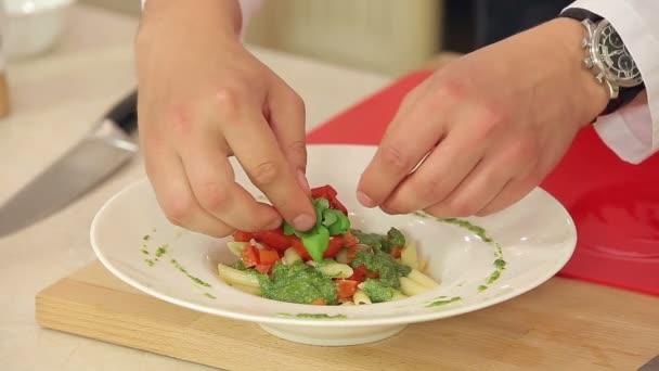 Šéfkuchař dát čerstvé bazalky a drcený pepř na těstoviny s zeleným pestem a smažené červené Cherry rajčátky na talíř