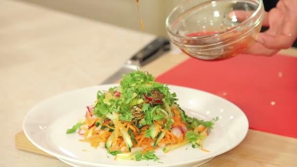 Lo chef è versando Dressing in appena tagliato Vegetable Salad, alimenti biologici, concetto di nutrizione sano