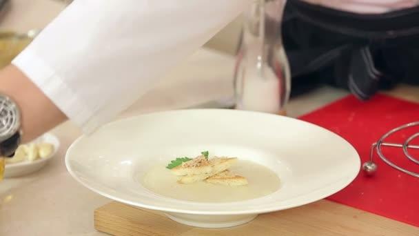 Kuchař je dávat kopr, petržel, sůl a pepř v destičce s Smetanová polévka, křupavé toasty a strouhaný sýr