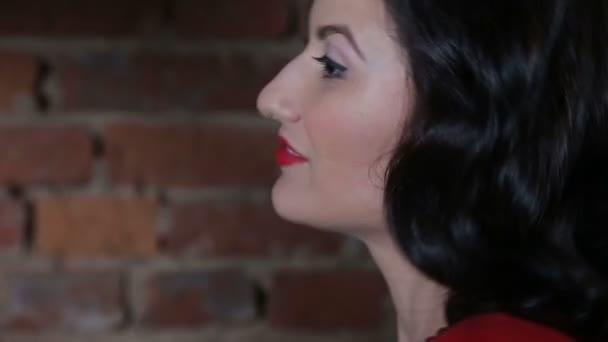 Sexy bruneta v červených šatech flirt, tanec a vystupují proti cihlové zdi