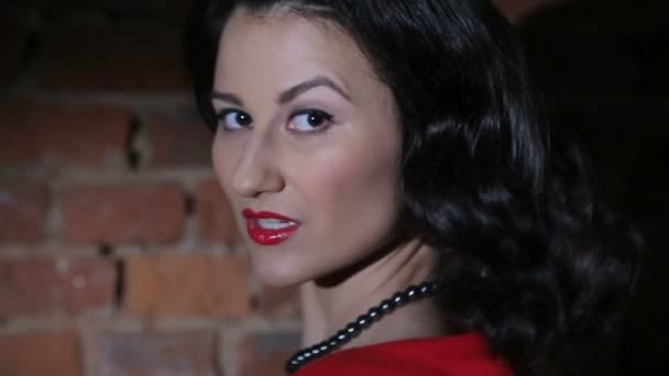 Sexy Brünette in roten Kleid, Flirten, tanzen und posieren gegen Rote Wand