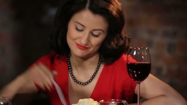 Romantické bruneta v červených šatech s růže, svíčky a víno s úsměvem, flirtování a při pohledu na fotografii muže
