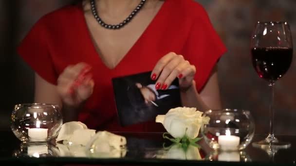 Romantické bruneta v červených šatech s růže, svíčky a víno s úsměvem, flirtování a trhání fotografii muže