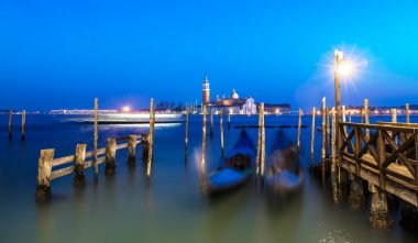 Venice night view seascape after sunset. Blurred Gondolas with l