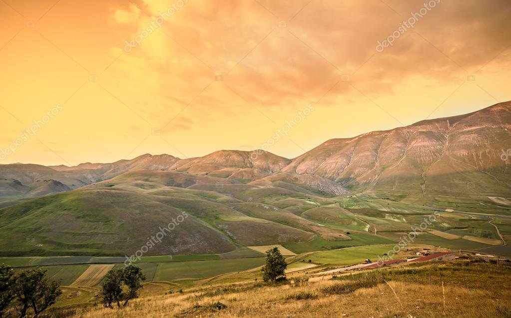 Warm sunset landscape. Mountains and fields background.