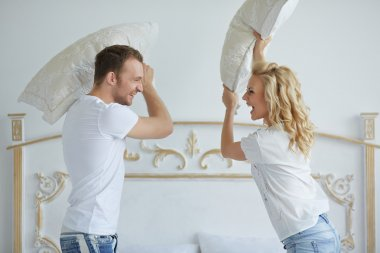 couple fighting with pillows