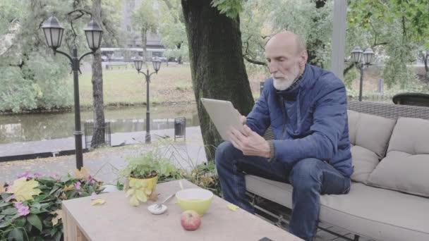 Rentner sitzt in warmer Jacke in Restaurant