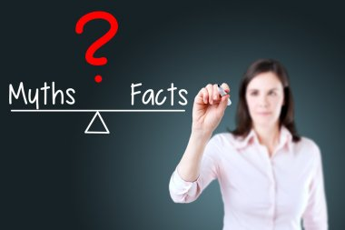Young business woman writing myths and facts compare on balance bar.