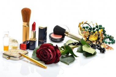 Women's perfumes, cosmetics and a flower in still life