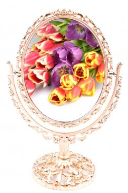 Bouquet of flowers tulips are reflected in the old gilded mirror on a white background