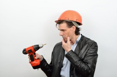 A man working in perplexity pondered look at a tool screw gun