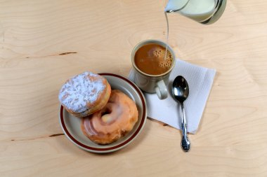 Two delicious sugared ring donuts served on white plate with a cup of hot drink
