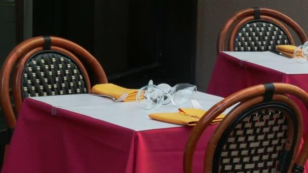 Několik klientů sedí v restauraci, zaměření na sklo s ubrouskem a hůlky u stolu