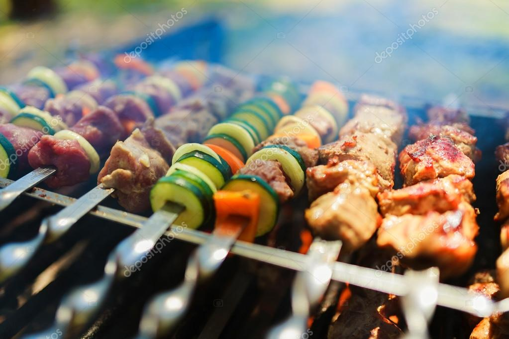 Meat and vegetable skewers on grill in nature