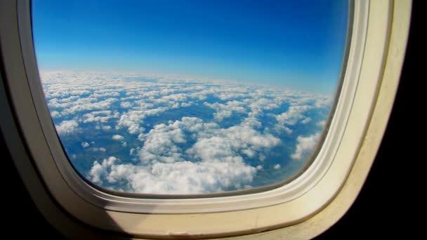 Repülőgép repül a kék égen át a fehér felhők. Kilátás az ablakból a repülőgép szárnya.
