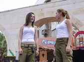 Beer-Sheva, Izrael-5 března 2015: Dvě dívky v bílých košilích a zelené kalhoty vojáci pohled na sebe při provádění na jevišti-Purim