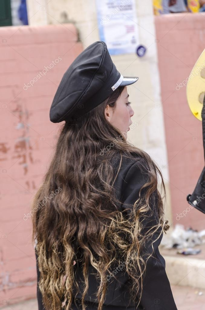 Beer-Sheva, ISRAEL - March 5, 2015: Girl with beautiful long hair in black police cap standing with her back -Purim