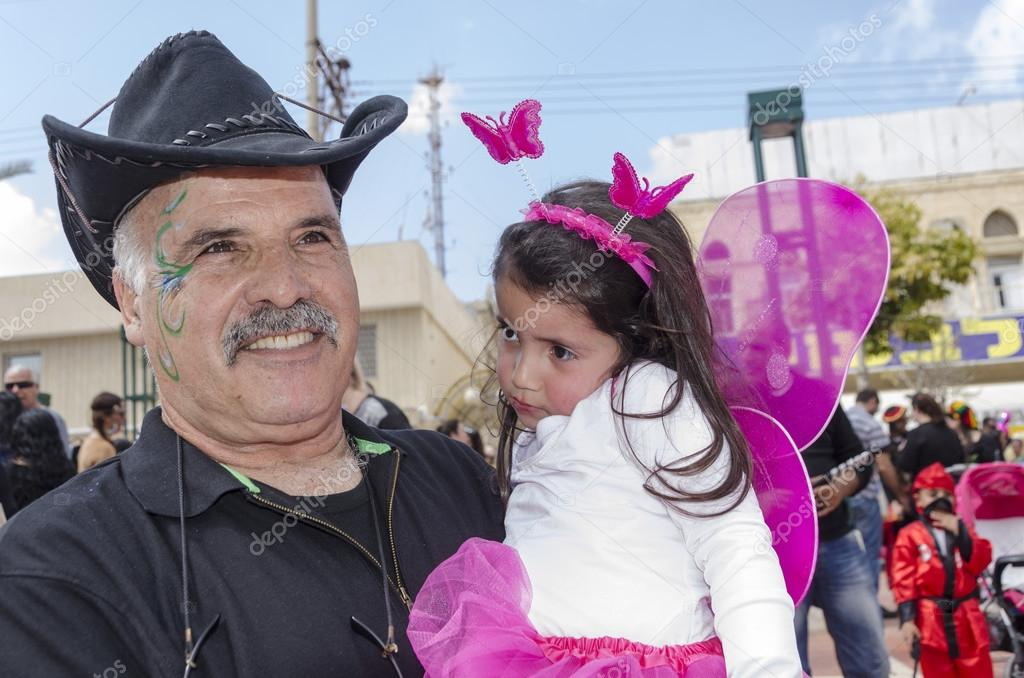 Beer-Sheva, ISRAEL - March 5, 2015:An elderly man with a mustache, with a festive make-up in black and a black cowboy hat and holds a little girl in a pink dress -  Purim