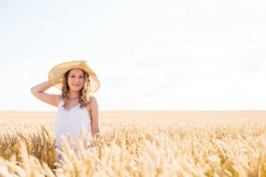 Beautiful young girl with her hat on, standing in wheat field at sunset. Selective focus. Toned in warm colors. stock vector