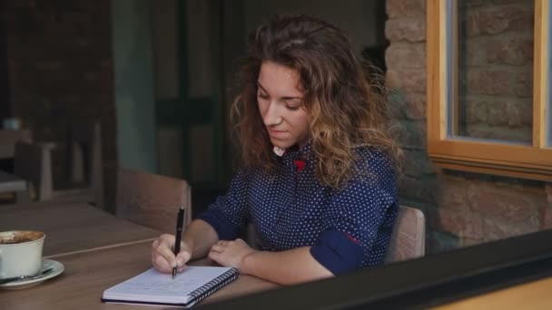 Girl drawing a cup of coffee in the notepad